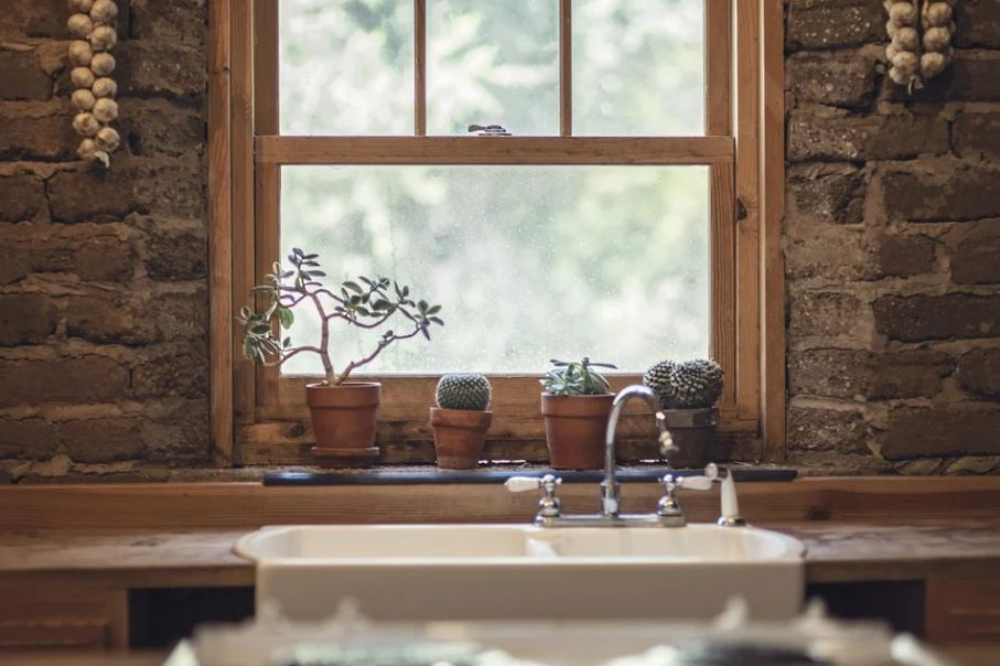 Picture of a brick wall featuring a window and a farmhouse sink.