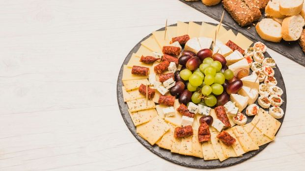 a close-up picture of a stone cheese board with smoked sausages and grapes